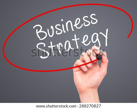 Man Hand writing Business Strategy with black marker on visual screen. Isolated on grey. Business, technology, internet concept. Stock Image - stock photo