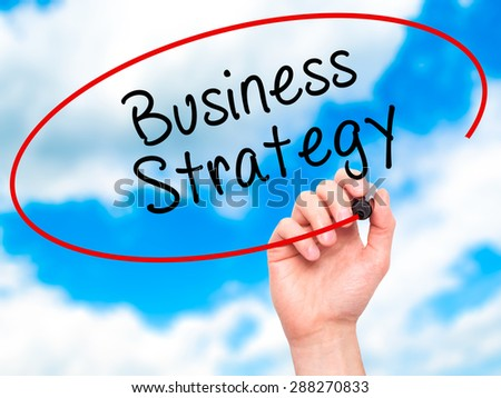 Man Hand writing Business Strategy with black marker on visual screen. Isolated on sky. Business, technology, internet concept. Stock Image - stock photo
