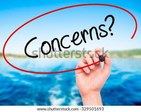 Man Hand writing Concerns? with black marker on visual screen. Isolated on nature. Business, technology, internet concept. Stock Photo - stock photo