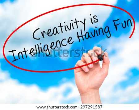 Man Hand writing Creativity is Intelligence Having Fun with black marker on visual screen. Isolated on sky. Business, technology, internet concept. Stock Photo - stock photo