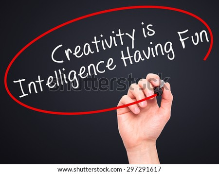 Man Hand writing Creativity is Intelligence Having Fun with black marker on visual screen. Isolated on black. Business, technology, internet concept. Stock Photo - stock photo