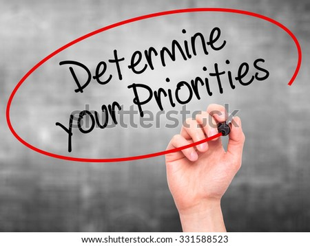 Man Hand writing Determine your Priorities with black marker on visual screen. Isolated on grey. Business, technology, internet concept. Stock Photo - stock photo
