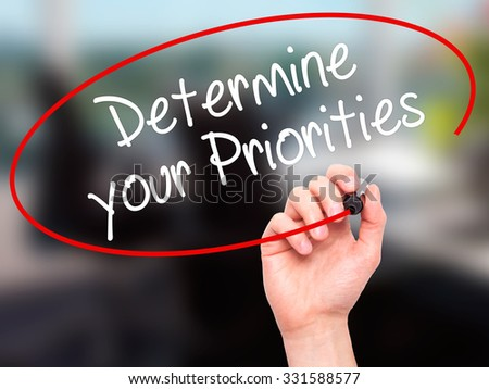 Man Hand writing Determine your Priorities with black marker on visual screen. Isolated on office. Business, technology, internet concept. Stock Photo - stock photo