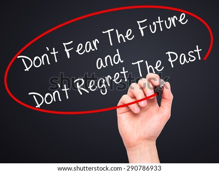 Man Hand writing Don't Fear The Future and Don't Regret The Past with black marker on visual screen. Isolated on black. Life, technology, internet concept. Stock Image - stock photo