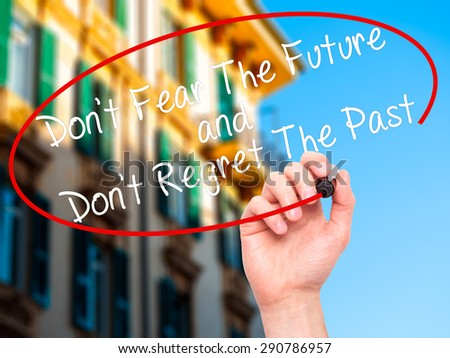 Man Hand writing Don't Fear The Future and Don't Regret The Past with black marker on visual screen. Isolated on nature. Life, technology, internet concept. Stock Image - stock photo