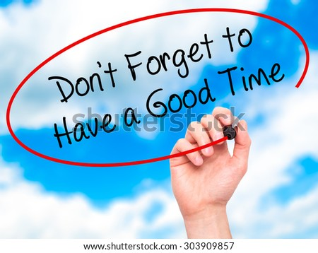 Man Hand writing Don't Forget to Have a Good Time with black marker on visual screen. Isolated on sky. Business, technology, internet concept. Stock Photo - stock photo
