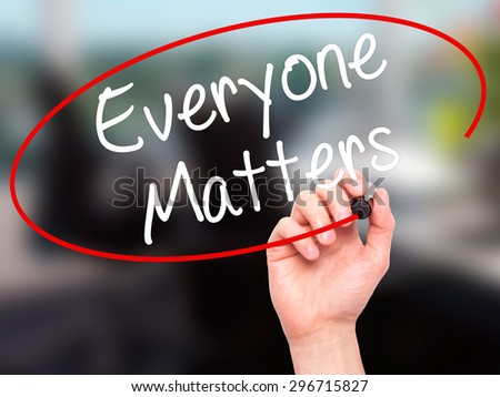 Man Hand writing Everyone Matters with black marker on visual screen. Isolated on office. Business, technology, internet concept. Stock Photo - stock photo