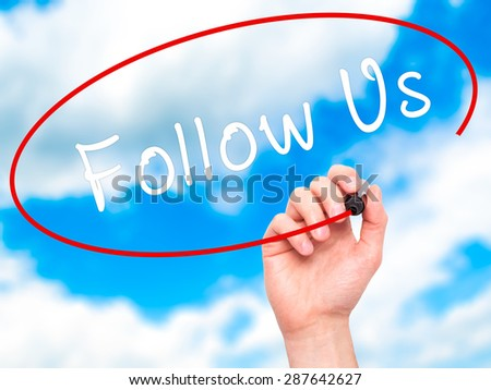 Man Hand writing Follow Us with black marker on visual screen. Isolated on sky. Business, technology, internet concept. Stock Image - stock photo
