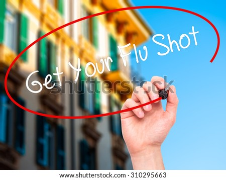 Man Hand writing Get Your Flu Shot with black marker on visual screen. Isolated on city. Business, technology, internet concept. Stock Photo - stock photo