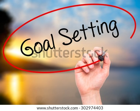 Man Hand writing Goal Setting  with black marker on visual screen. Isolated on nature. Business, technology, internet concept. Stock Photo - stock photo