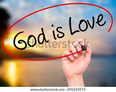 Man Hand writing God is Love with black marker on visual screen. Isolated on nature. Business, technology, internet concept. Stock Photo - stock photo