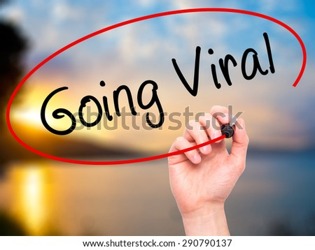 Man Hand writing Going Viral with black marker on visual screen. Isolated on nature. Business, technology, internet concept. Stock Image - stock photo