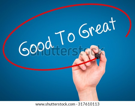 Man Hand writing Good To Great with black marker on visual screen. Isolated on blue. Business, technology, internet concept. - stock photo