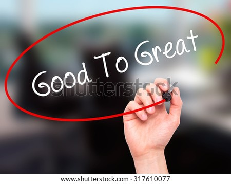 Man Hand writing Good To Great with black marker on visual screen. Isolated on office. Business, technology, internet concept. - stock photo
