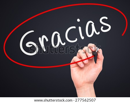 Man Hand writing Gracias with marker on transparent wipe board. Isolated on black. Business, internet, technology concept.  Stock Photo - stock photo