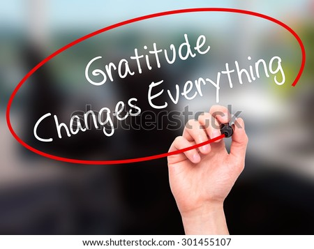 Man Hand writing Gratitude Changes Everything with black marker on visual screen. Isolated on office. Business, technology, internet concept. Stock Photo - stock photo
