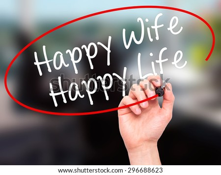 Man Hand writing Happy Wife Happy Life with black marker on visual screen. Isolated on office. Business, technology, internet concept. Stock Photo - stock photo