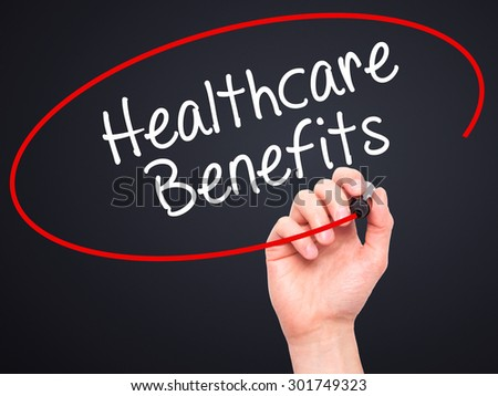 Man Hand writing Healthcare Benefits with black marker on visual screen. Isolated on black. Business, technology, internet concept. Stock Photo - stock photo