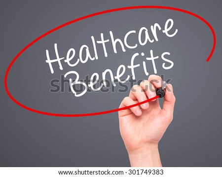 Man Hand writing Healthcare Benefits with black marker on visual screen. Isolated on grey. Business, technology, internet concept. Stock Photo - stock photo