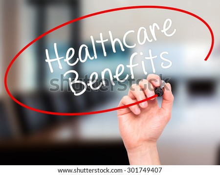 Man Hand writing Healthcare Benefits with black marker on visual screen. Isolated on office. Business, technology, internet concept. Stock Photo - stock photo