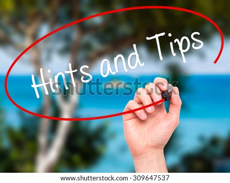Man Hand writing Hints and Tips with black marker on visual screen. Isolated on nature. Business, technology, internet concept. Stock Photo  - stock photo