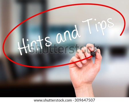 Man Hand writing Hints and Tips with black marker on visual screen. Isolated on office. Business, technology, internet concept. Stock Photo  - stock photo