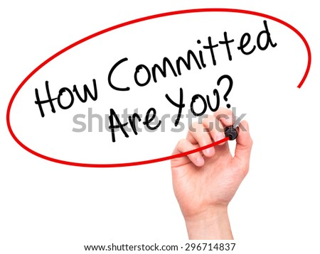 Man Hand writing How Committed Are You? with black marker on visual screen. Isolated on white. Business, technology, internet concept. Stock Photo - stock photo