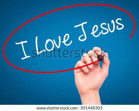 Man Hand writing I Love Jesus with black marker on visual screen. Isolated on blue. Business, technology, internet concept. Stock Photo - stock photo