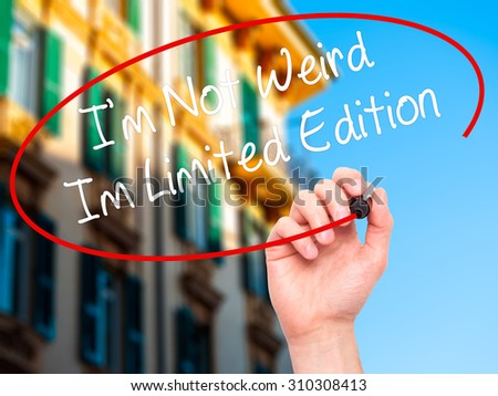 Man Hand writing I'm Not Weird Im Limited Edition with black marker on visual screen. Isolated on city. Business, technology, internet concept. Stock Photo - stock photo
