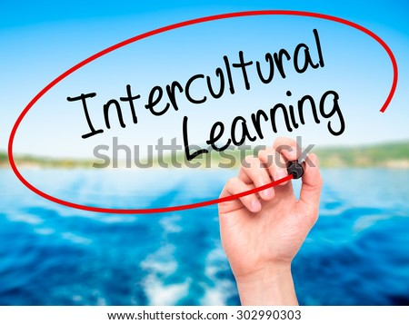 Man Hand writing Intercultural Learning with black marker on visual screen. Isolated on nature. Business, technology, internet concept. Stock Photo - stock photo