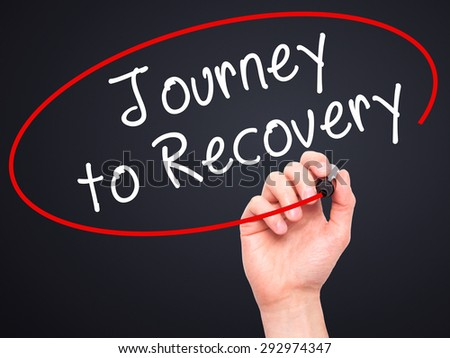 Man Hand writing Journey to Recovery with black marker on visual screen. Isolated on black. Life, technology, internet concept. Stock Image - stock photo