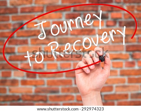 Man Hand writing Journey to Recovery with black marker on visual screen. Isolated on bricks. Life, technology, internet concept. Stock Image - stock photo