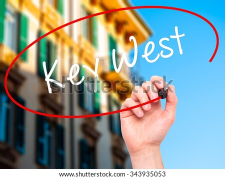 Man Hand writing Key West with black marker on visual screen. Isolated on background. Business, technology, internet concept. Stock Photo - stock photo