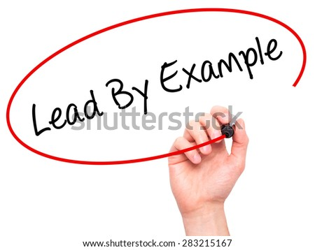 Man Hand writing Lead By Example with marker on transparent wipe board. Isolated on white. Business, internet, technology concept. Stock Photo - stock photo