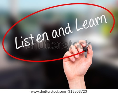 Man Hand writing Listen and Learn with black marker on visual screen. Isolated on office. Business, technology, internet concept. Stock Photo - stock photo