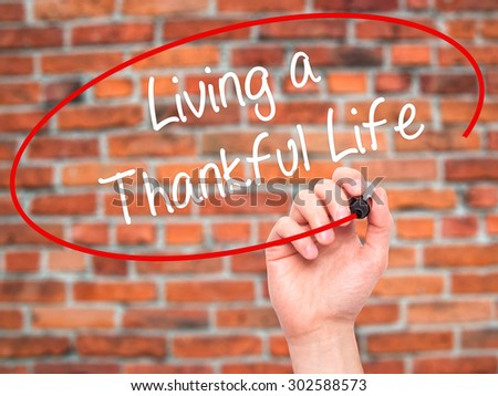 Man Hand writing Living a Thankful Life with black marker on visual screen. Isolated on bricks. Business, technology, internet concept.  - stock photo