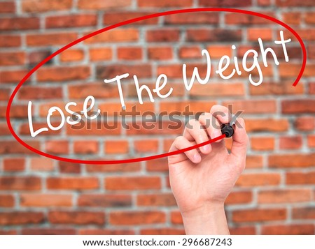 Man Hand writing Lose The Weight with black marker on visual screen. Isolated on bricks. Business, technology, internet concept. Stock Photo - stock photo