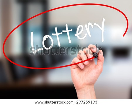 Man Hand writing Lottery  with black marker on visual screen. Isolated on office. Business, technology, internet concept. Stock Photo - stock photo