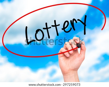 Man Hand writing Lottery  with black marker on visual screen. Isolated on sky. Business, technology, internet concept. Stock Photo - stock photo