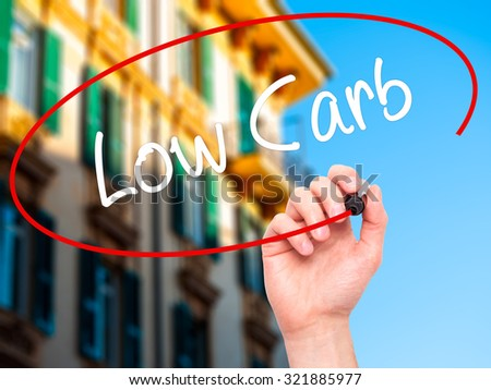 Man Hand writing Low Carb with black marker on visual screen. Isolated on city. Business, technology, internet concept. - stock photo