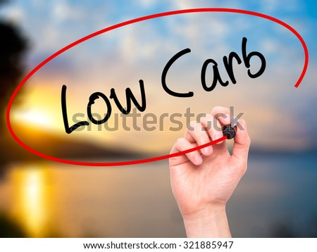 Man Hand writing Low Carb with black marker on visual screen. Isolated on nature. Business, technology, internet concept. - stock photo