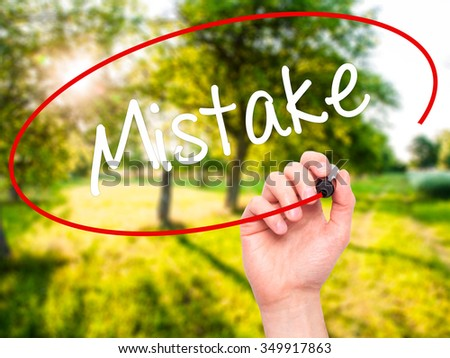 Man Hand writing Mistake with black marker on visual screen. Isolated on background. Business, technology, internet concept. Stock Photo - stock photo