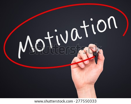 Man Hand writing Motivation with marker on transparent wipe board. Isolated on black. Business, internet, technology concept.  Stock Photo - stock photo