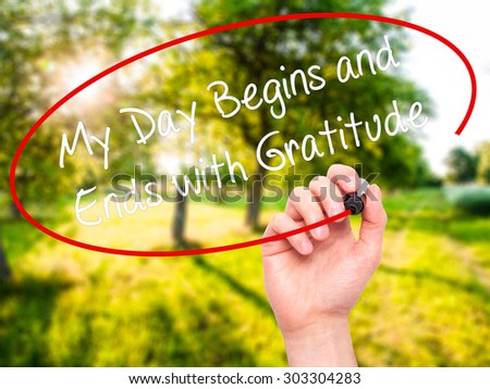Man Hand writing My Day Begins and Ends with Gratitude with black marker on visual screen. Isolated on nature. Business, technology, internet concept. Stock Photo - stock photo