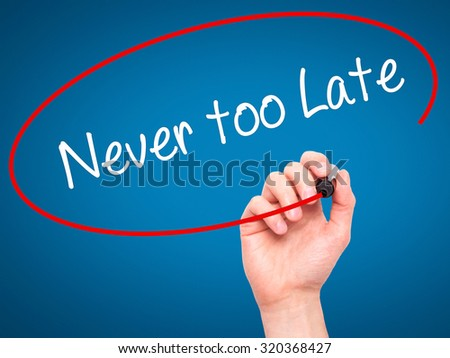 Man Hand writing Never too Late with black marker on visual screen. Isolated on blue. Business, technology, internet concept. - stock photo