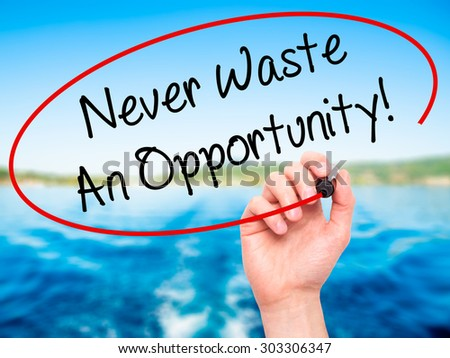 Man Hand writing Never Waste An Opportunity! with black marker on visual screen. Isolated on nature. Business, technology, internet concept. Stock Photo - stock photo