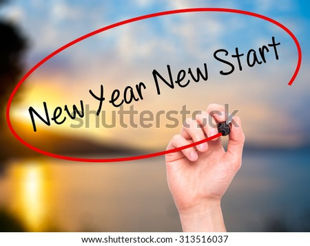 Man Hand writing New Year New Start with black marker on visual screen. Isolated on nature. Business, technology, internet concept. Stock Photo - stock photo