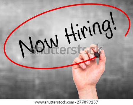 Man Hand writing Now Hiring! with marker on transparent wipe board. Isolated on grey. Business, internet, technology concept.  Stock Photo - stock photo