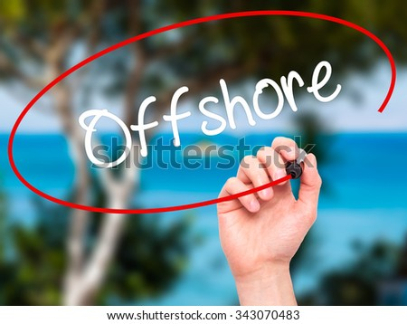 Man Hand writing Offshore with black marker on visual screen. Isolated on nature. Business, technology, internet concept. Stock Photo - stock photo