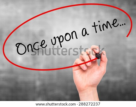 Man Hand writing Once upon a time... with black marker on visual screen. Isolated on grey. Business, technology, internet concept. Stock Image - stock photo